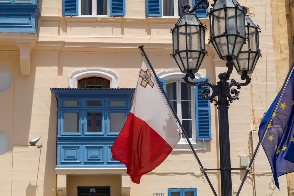 Malta e bandeira da UE na frente da tradicional varanda azul maltesa, com lampost velho, Valletta, Malta