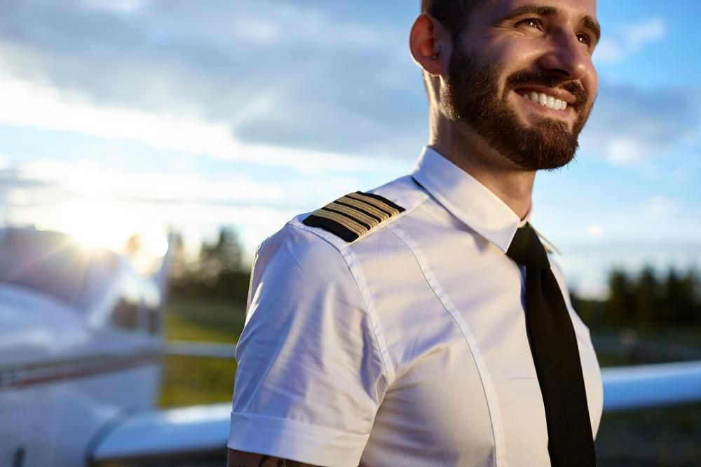 Portrait of young pilot in uniform posing with a happy toothy smile with air craft on the background. Backlit sunny photo