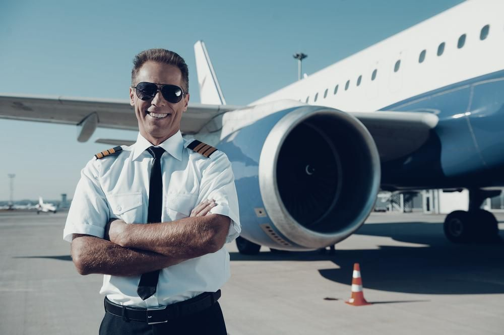 Juruterbang yang yakin. Juruterbang lelaki yang yakin dalam penyelamatan seragam menyeberang dan tersenyum dengan pesawat di latar belakang