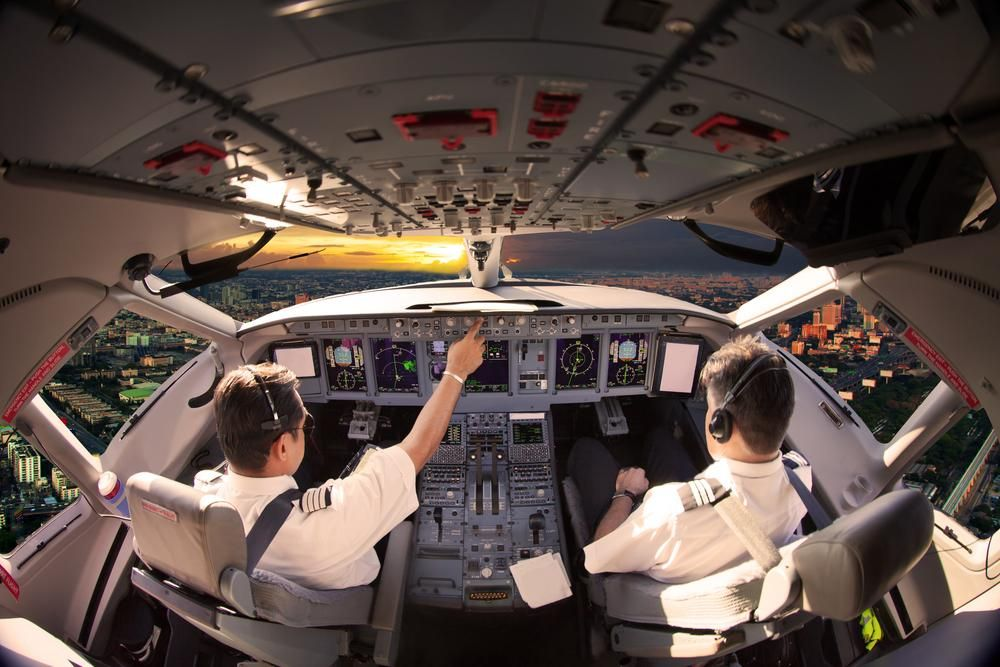 Flight Deck of modern aircraft. Pilots at work. Sunset view from the plane cockpit.