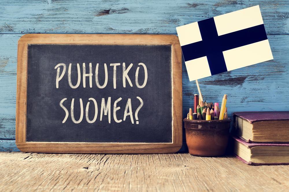 um quadro-negro com a pergunta puhutko suomea, você fala finlandês? escrito em finlandês, uma panela com lápis, alguns livros e a bandeira da Finlândia, em uma mesa de madeira